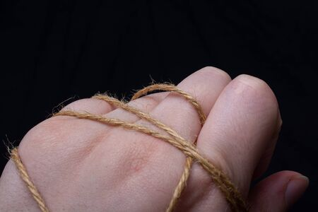 A female's hand wrapped in  string Standard-Bild
