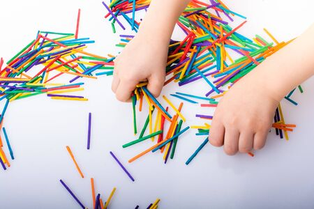 Kid playing with coloured wooden sticks for creativity on white background