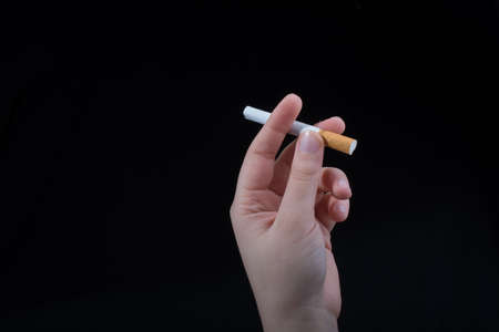 Hand is holding a cigarette on black background 免版税图像