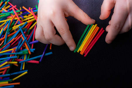 Kid playing with coloured wooden  sticks for creativity on white background Banco de Imagens