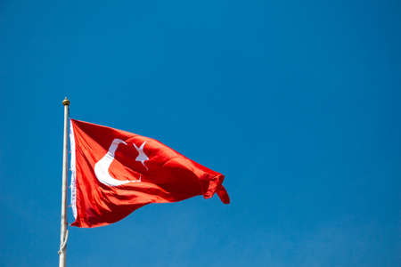 Turkish national flag with white star and moon on a pole in sky 免版税图像