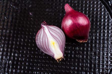 Red onion bulb cut in half on a certain  background 版權商用圖片