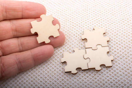 Hand holding piece of jigsaw puzzle as problem solution concept 版權商用圖片