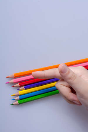 Hand holding color Pencils placed on a white background