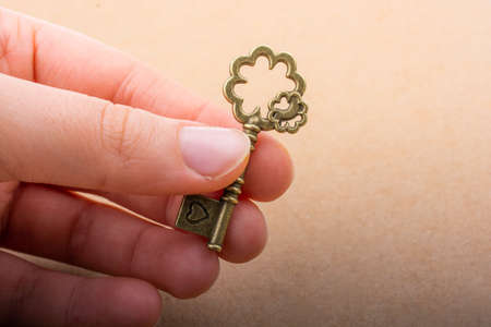 Hand holding a retro styled decorative key in hand