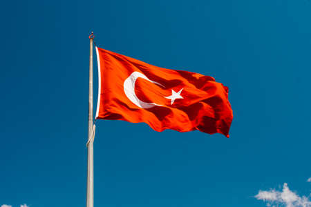 Turkish national flag with white star and moon on a pole in sky Stok Fotoğraf