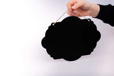 Black speech bubble shaped notice board in hand on white background