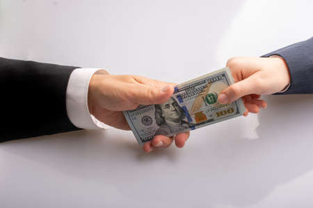 Businessman giving and receiving  US dollar banknote money