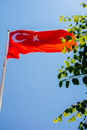 Turkish national flag with white star and moon on a pole in sky Stock fotó