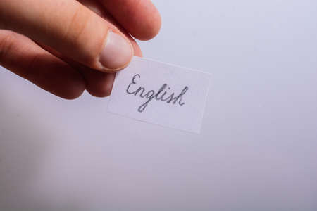 Hand holding notepaper with English wording on white background