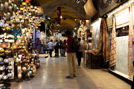 Interior view of the Grand Bazaar. Tourists shopping in the Grand Bazaar.