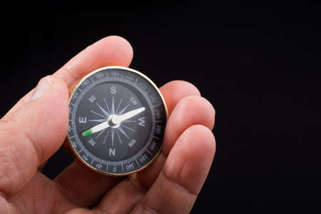 Child hand holding a compass on a black background