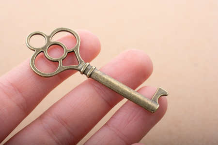 Hand holding a retro styled decorative key in hand Imagens