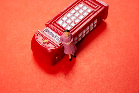 Classical British style Red phone booth model and woman figurine on red Stock Photo