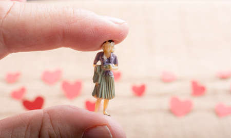 Woman figurine and Love concept with paper heart on threads Stock Photo