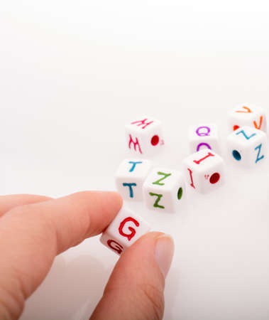 Colorful alphabet letter cubes in handon a white background