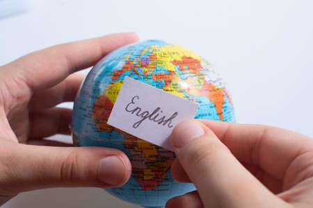 Hand holding notepaper with English wording on model globe Imagens