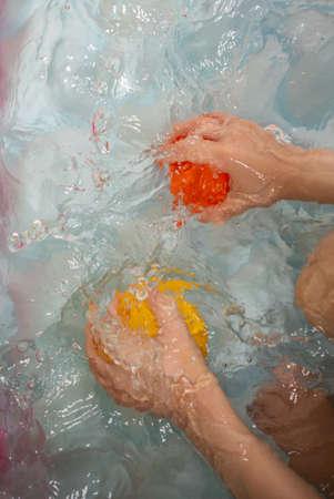 Child splashing water and plying with balls