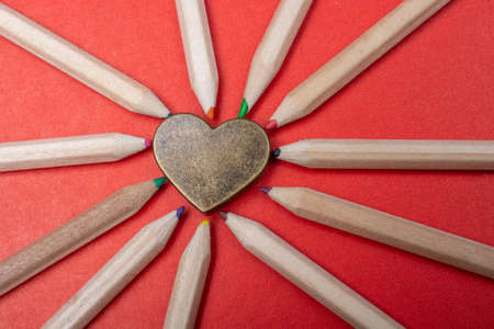 Heart laid out with sharpened multi-colored pencils Standard-Bild