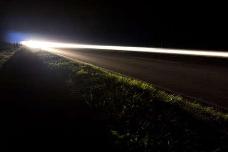 Autoscheinwerfer auf einer Straße bei Nacht