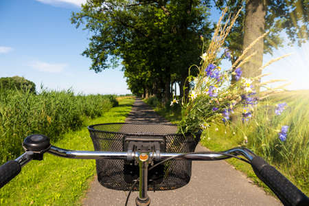 cycling on way in landscape with sunlight and blue sky Stock Photo