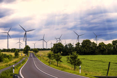 wind generators in landscape with a road and cloudy sky with sunbeams
