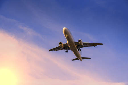 passenger plane: rising airplane in blue violet sky and sunlight