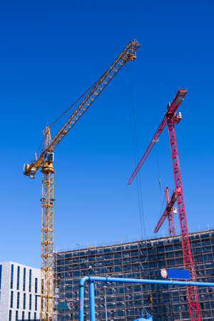 economic revival: construction site with orange and red cranes and blue summer sky