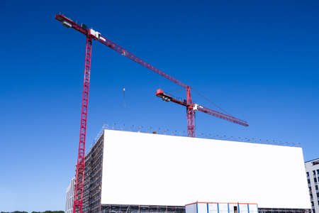 commercial real estate: construction site and blank billboard and blue sky