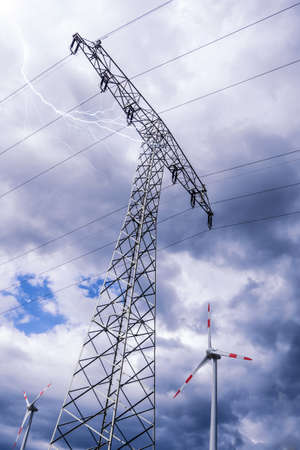 electricity providers: electrical tower and wind generator and storm clouds (alternative energy)