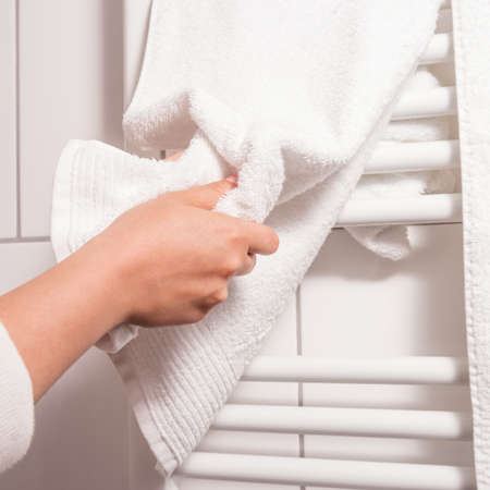 dry hands on a towel, heating in background photo
