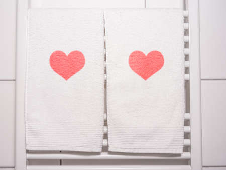 red hearts on towel on a heating in bathroom photo