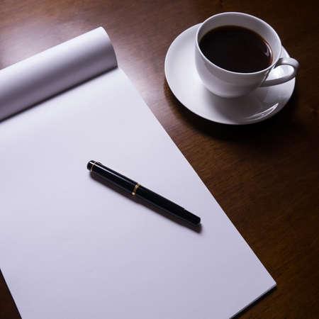 mesa com caneta-tinteiro, folha de papel, copo de caf
