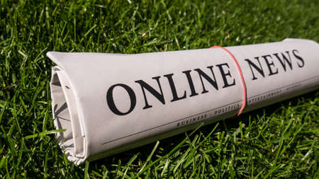 lates: online newspaper on green meadow Stock Photo