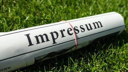 impressum newspaper on green meadow photo