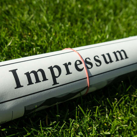 impressum newspaper on green meadow photo
