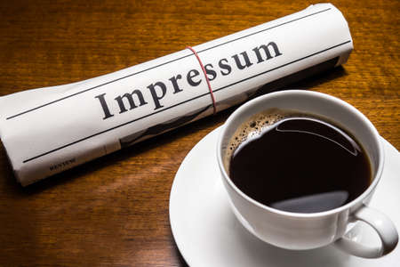 impressum newspaper, cup of coffee on desk photo