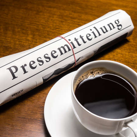 lates: pressemitteilung, cup of coffee on desk Stock Photo