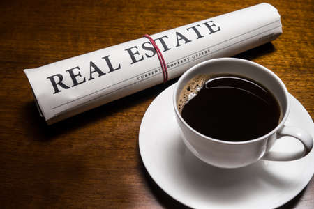 real estate newspaper, cup of coffee on desk