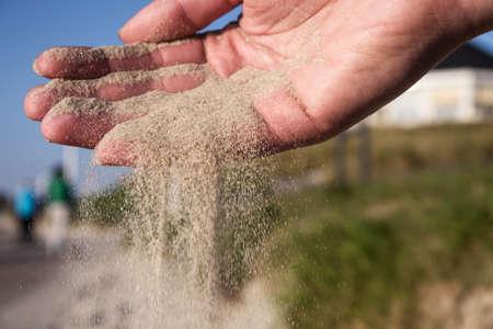 trickle down: Sand running through hands on beach