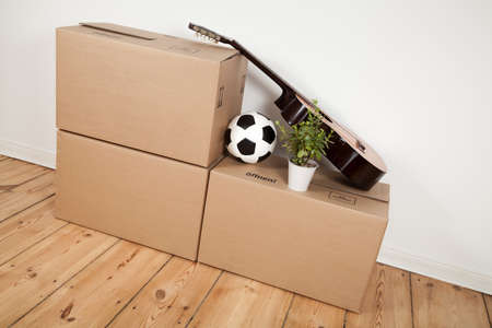 moving boxes, guitar and football in room photo