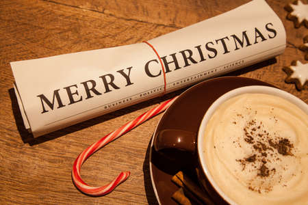 merry christmas newspaper, cup of capuccino and candy cane photo