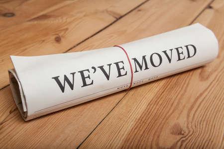 """""""Wir sind umgezogen"""" Zeitung auf Holzboden"""