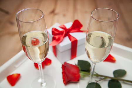 evening newspaper: champagne glasses and red rose on tray