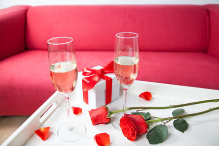 evening newspaper: champagne glasses and red rose in living room