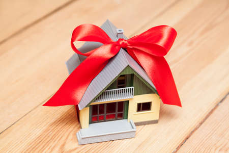 house with red ribbon on wooden floor photo