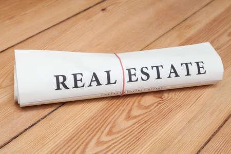 lates: real estate newspaper on wooden floor Stock Photo