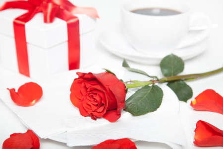 red rose, present box and cup of coffee on white table photo