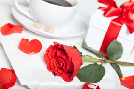 red rose, present box and coffee on table photo
