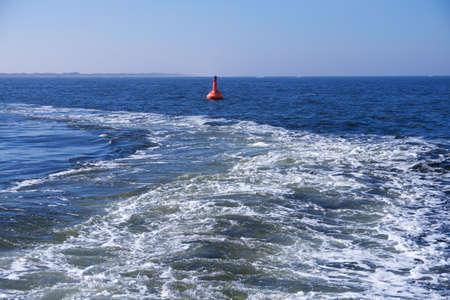 corrugation: buoy on sea, in background island